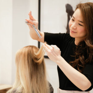 Japanese Hairstylist and Artistic Director Yoko, cutting a client's hair